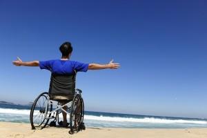 insurance: man in wheelchair enjoying the  beach