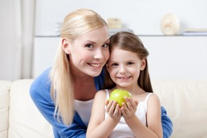 Smiley mummy with her keeping sweet green apple daughter