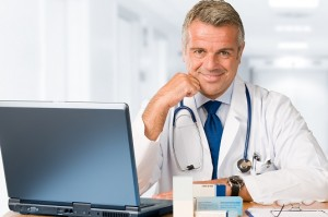 Happy satisfied mature doctor working and looking at camera in his modern clinic office