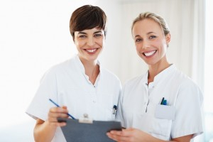 Portrait of female healthcare professionals smiling and discussing medical report