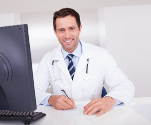 Smiling Medical Doctor With Stethoscope Sitting At A Desk