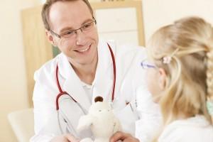 Kind gibt Arzt ein Stofftier als Dank