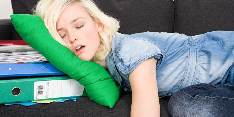 Mujer-joven-perezosa-dormida-en-un-sillon-negro-apoyando-su-cabeza-en-un-cojin-verde-donde-debajo-hay-un-archivador-y-varios-papeles-d